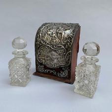 Lot.22 Coffret nécessaire à parfum, argent repoussé et cuir. Contient deux flacons en cristal légèrement tronconiques à pans avec leurs bouchons. XVIIIe siècle H. 14 cm – L. 10 cm P. 5,5 cm - Est.250/300 €