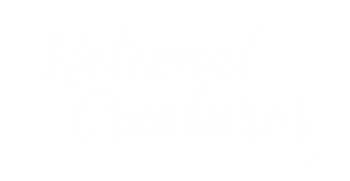 """The Rational Creatures Logo: """"rational cratures"""" written in a white, script font"""