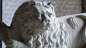 Rigai, katonai sírokat őrző oroszlán szigorú nézéssel.