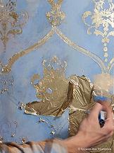 Каменная стена с осыпающейся штукатуркойи золотым орнаментом