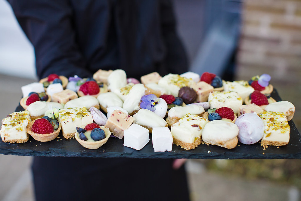 A delectable selection of dessert canapes: rich coffee éclairs, light rose water and pistachio cheesecakes and wonderfully refreshing summer berry tartlets.