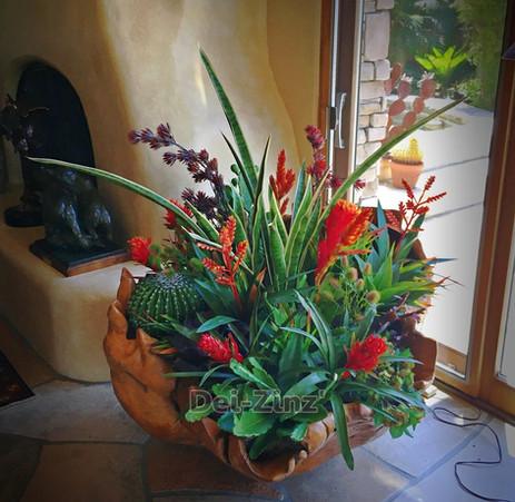 faux cactus garden in large wooden vessel