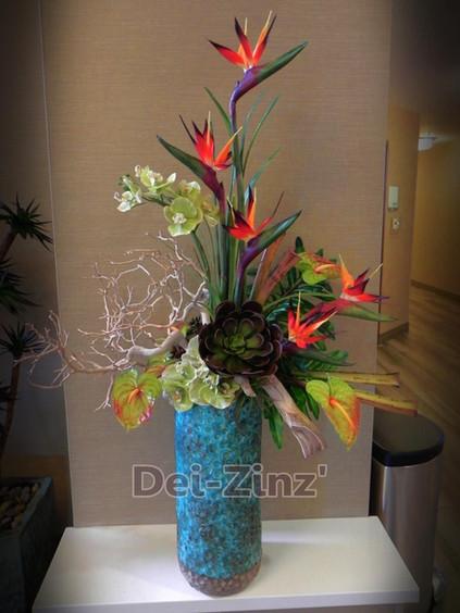tropical arrangement in tall teal vase