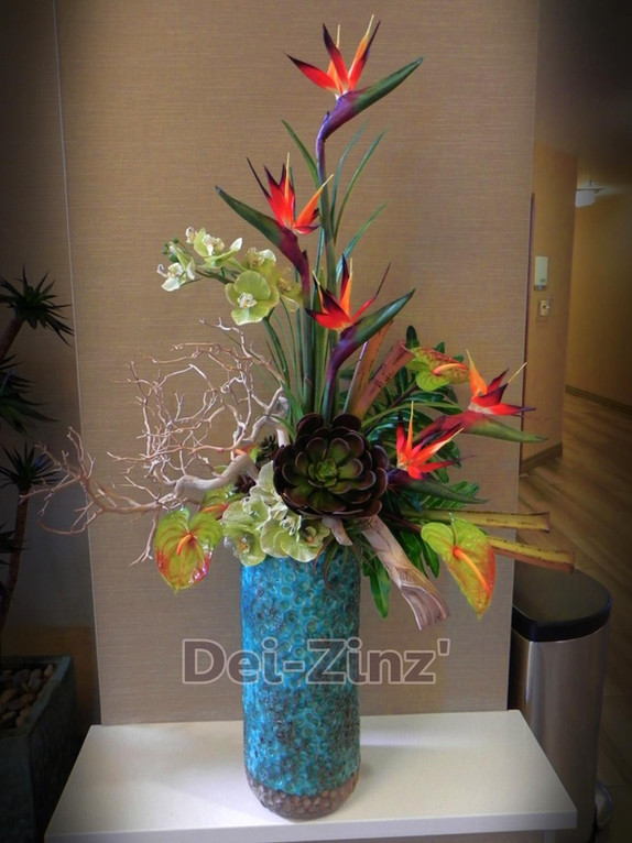 tropical arrangement in tall teal vase