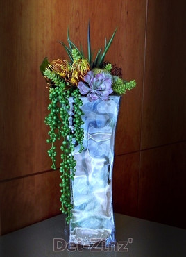 faux suculent arrangement in crystal vase