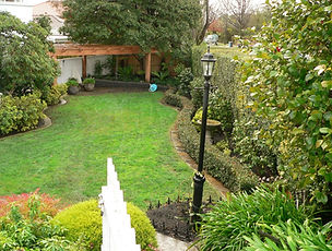 Back yard garden with lawn surrounded by hedges