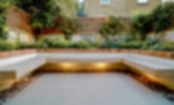 Large garden bench with lights underneath in a garden built with paving and brick walls