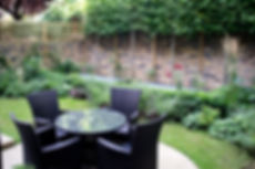 Garden with pleached lime trees, lawn, planting and an outdoor dining set on York stone patio
