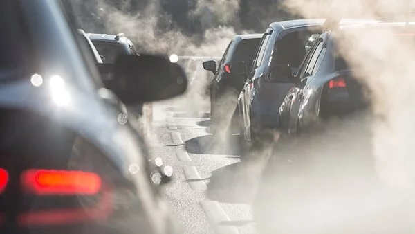 Que of cars stuck in traffic, surrounded by exhaust fumes