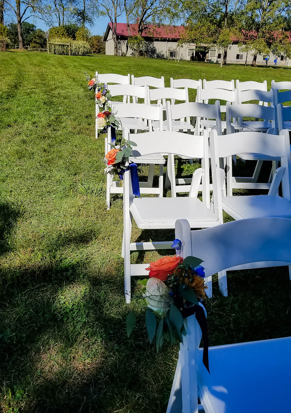 Outdoor wedding ceremony adorned the chairs with flowers at Woods Edge Farm