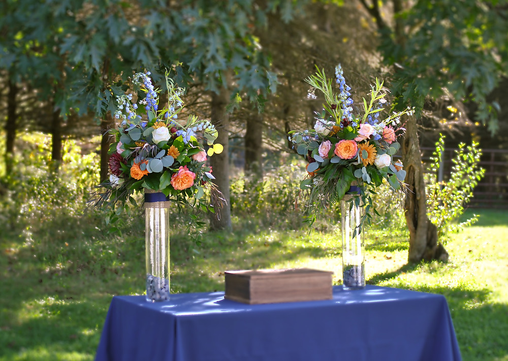 Tall floral arrangements adorned the outdoor wedding ceremony at Woods Edge