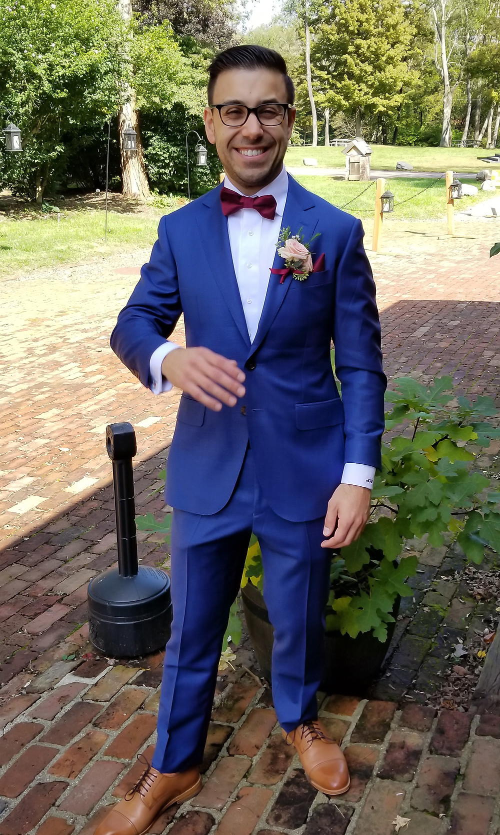 Groom in his blue suit and blush boutonniere