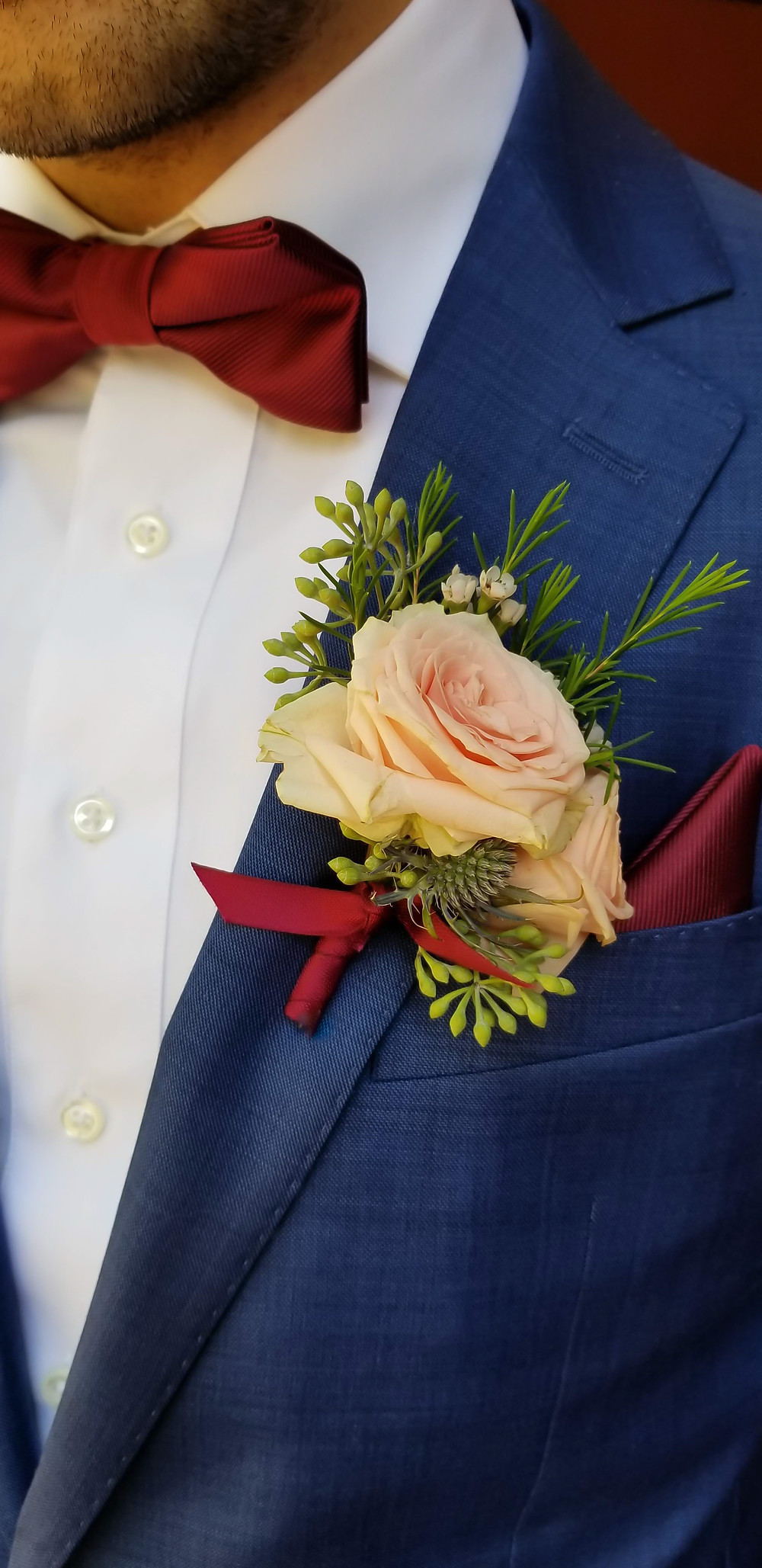 Groom in blue suit with rose blush buttoniere