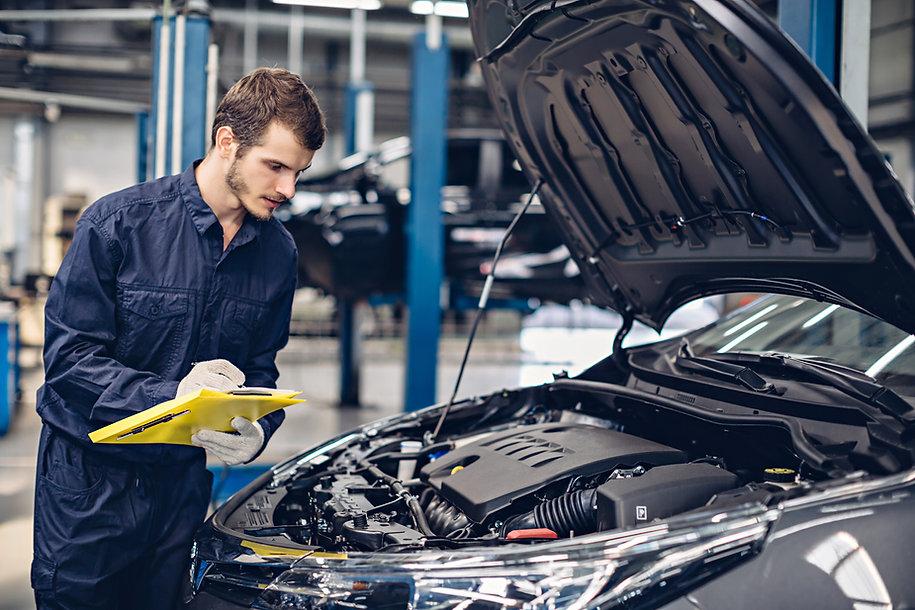 Auto car repair service center. Mechanic examining car engine.jpg