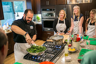 Chef Mark and home owners wih friends cookig at an event