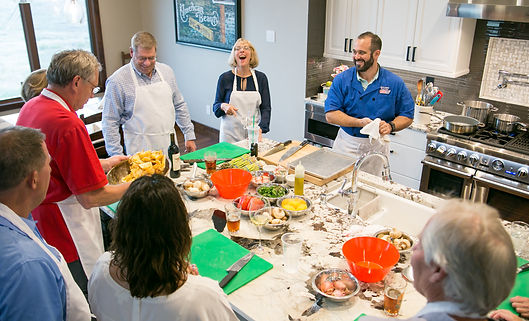 Home Owners and friends having fun with Chef Mark cooking in their new kitchen