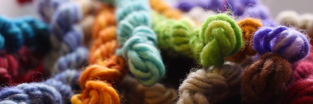 Dream in Color mini skeins in blue, purple, green, orange, brown, and pink.