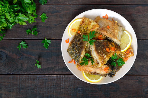 Pieces of roasted carp with lemon and gr