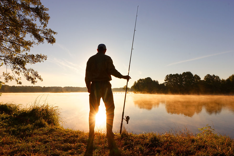 Silhouette of angler standing on the lak