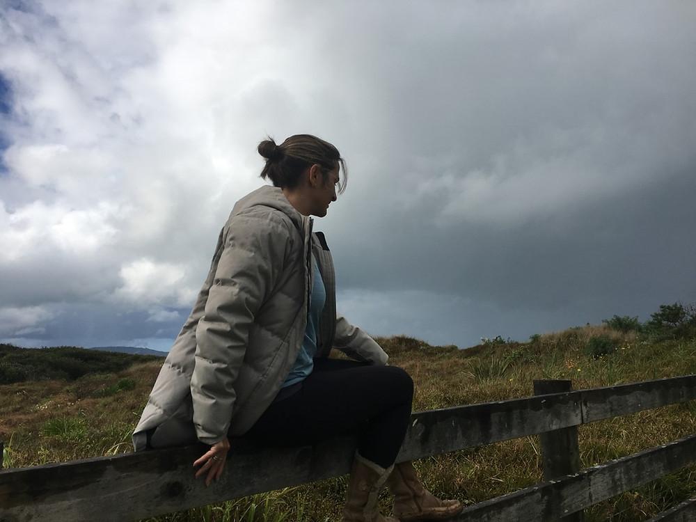 Femme assise sur une clôture