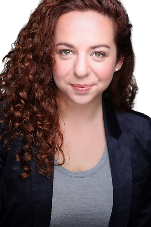 Emma, a white woman with curly red hair, gazes into the camera with a slight smirk. She is wearing a navy blue velvet blazer over a gray t-shirt.