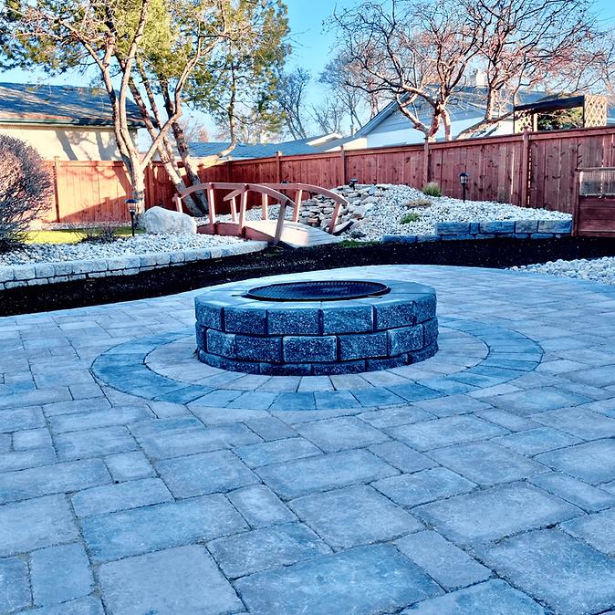 Full backyard landscape installation, Barkman Concrete stackstone firepit, roman pavers, custom inlay - Winnipeg, Manitoba