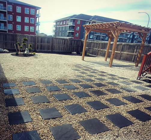 Beautiful Japanese styled yard with pergola and Barkman Concrete's brookeside slabs in the charcoal colour constructed for clients in Winnipeg