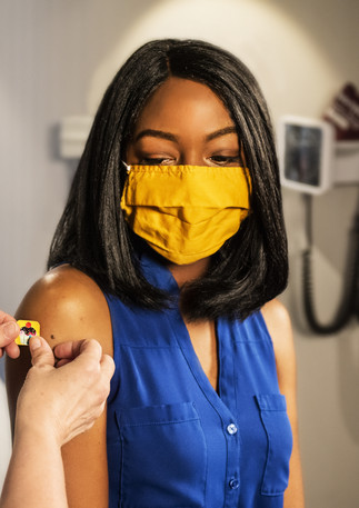 woman with blue button up shirt getting test with face mask on