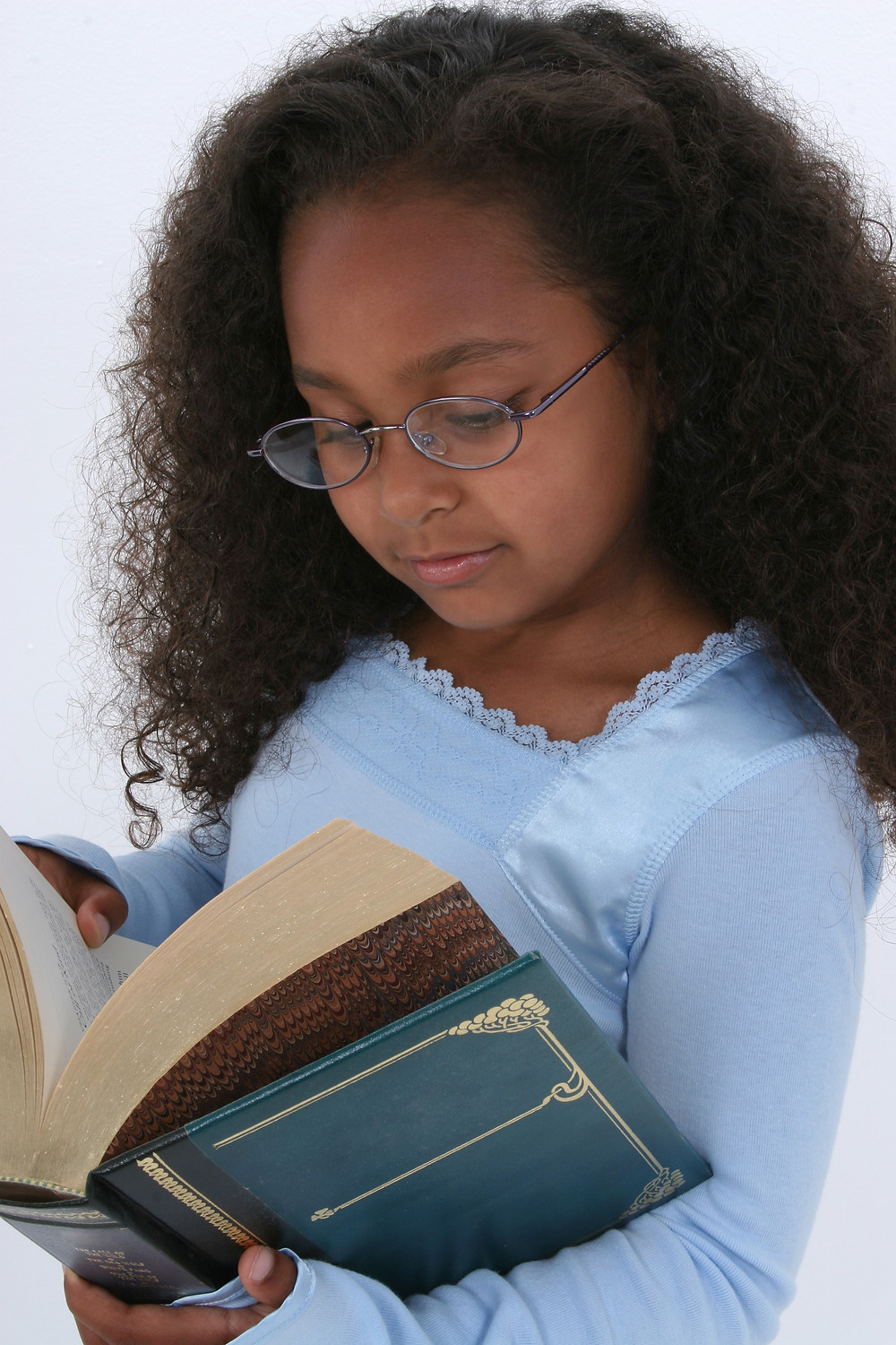 Beautiful Six Year Old In Glasses Readign Large Book.jpg