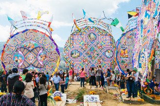 """Every year on November 1st, Guatemala's cemeteries become the setting of a colorful party to celebrate the life of those who have passed.   Giant kites called """"Barriletes"""" are prepared months in advance by youth cultural groups, with messages to send above as """"telegrams"""" for the dead."""