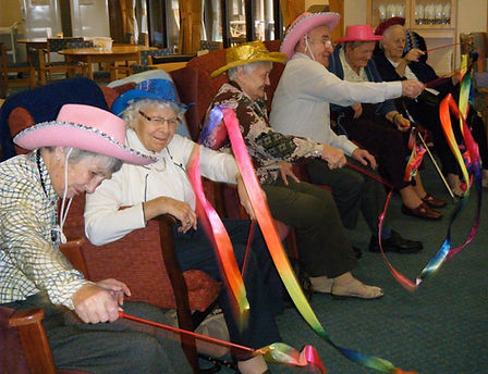 Six elderly people, seated and using ribbon streamers