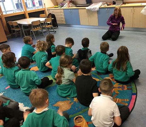 Diana telling a story to a class of primary schoolchildren