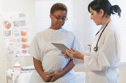 Pregnant black person with doctor