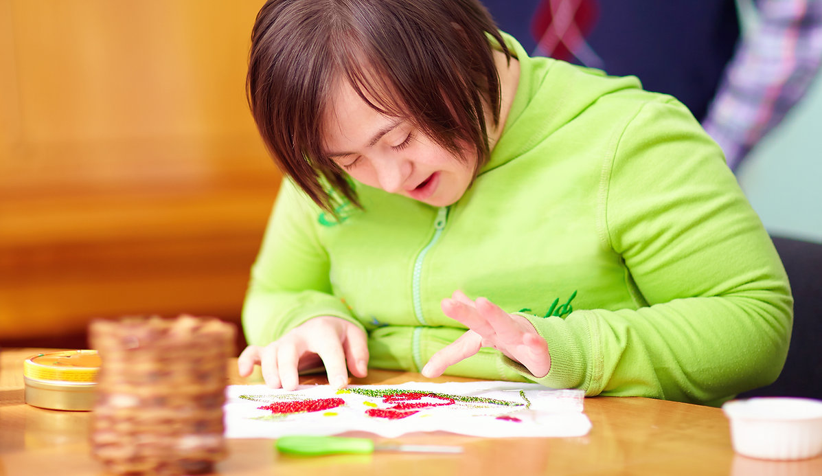 young adult woman with disability engaged in craftsmanship in rehabilitation center.jpg