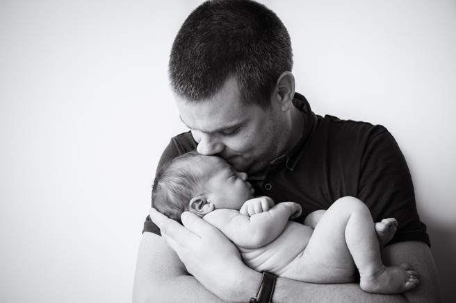 Father kissing his newborn baby