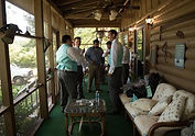 People standing on a porch getting dressed and ready for a wedding
