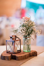 A center piece - a ceder plank with a jar full of flowers and a lantern