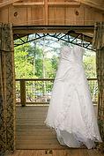A wedding dress hanging in the doorway
