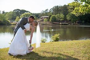 A wedding couple beside a lake kissing