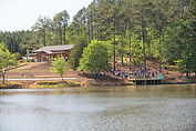 A lake, a dock with people standing on it getting married.  A barn and a wooded setting