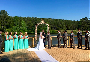 A couple on a dock getting married with their bridesmaids and groomsmen with them
