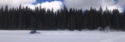 Snowmobile flying through open terrain