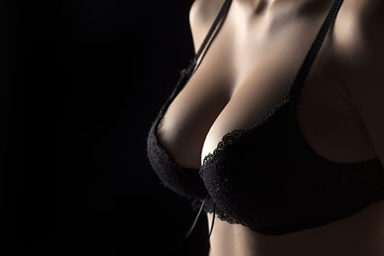 Woman's breast with a black bra on black background