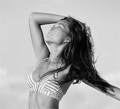 A happy young woman with swimwear top outdoor