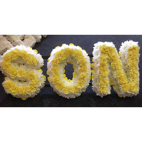 Massed Son Floral Tribute with a carnation centre.