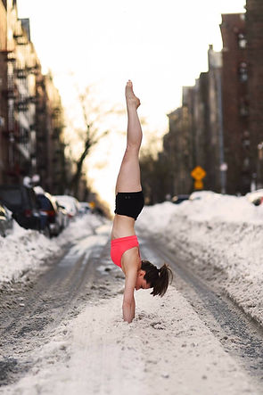 Woman doing a handstand in sports bra and shorts in the middle of a snowy New York City street