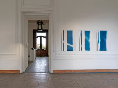 "Materia Prima - Museo d'Arte Contemporanea Castello di Rivara 2016   Cianotipi  Cyanotype on paper 122x82 cm   Materia Prima could be seen as one of the many possible outcomes of Bepi Ghiotti's work on the neo-baroque (space of) Castle of Rivara. Only one of the possible results, reasonably, determined by having to set a time limit to his tireless research. Yet, there is a moment before, at the beginning of the artist's operation on the location, in which time has already overwhelmingly taken its share as a raw material. Bepi's trained photographer eye recognizes the majesty of time, which is manifested in the traces of life and art deposited in the Castle's ambient by the passage of time.  His work thus concentrates on an attempt to resurface the essence of this space, almost sweeping away, one after the other, all the layers of recent history.  ​  Room after room, wall after wall, Ghiotti analyzes the geometries, listening to them breathe. Like a chemist in an ancient laboratory, he captures the light coming through the windows in different hours throughout the day. The light continuously changes, as does the perception of the architectures, thus delivering an essential experience of the location, through the artist's installation. The rooms of the neo-baroque villa, similar to living organisms, bring out the primary elements of their physiology: the asynchronous pulse of the two projectors beaming pure light, installed in the entryway; along the electromagnetic vibrations captured with ancient gestures on the cyanotypes, in the partial views of faces and landscapes that can only be imagined through scratches of light, torn away from the black of darkness,  of oblivion.  ​  Through this intervention, which is almost an archaeological operation on  the location, soaked in anthropological suggestions and ancient techniques,  Bepi Ghiotti reveals the heart to the audience. The viewer is led to the ""source"" of the identity of those rooms from the Eighteen hundreds, recovered through the artist's tenacious experience inside the Caslte and that of all its physical and unworldly dwellers. Walking through those rooms, among objects revealing the essence, one has the clear feeling of being inside a fully developing process, deeply interconnected with the ponderously conquered relationship the artist has had with the Castle of Rivara, day after day, in the resounding loneliness of those huge, empty rooms."