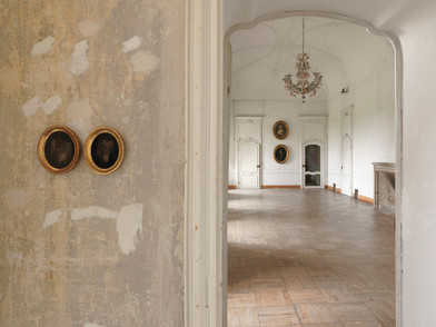 "Materia Prima - Museo d'Arte Contemporanea Castello di Rivara 2016   I Bui  Black paint, glass, wood,  XVII-XVIII century painting, gold Variable dimensions   Materia Prima could be seen as one of the many possible outcomes of Bepi Ghiotti's work on the neo-baroque (space of) Castle of Rivara. Only one of the possible results, reasonably, determined by having to set a time limit to his tireless research. Yet, there is a moment before, at the beginning of the artist's operation on the location, in which time has already overwhelmingly taken its share as a raw material. Bepi's trained photographer eye recognizes the majesty of time, which is manifested in the traces of life and art deposited in the Castle's ambient by the passage of time.  His work thus concentrates on an attempt to resurface the essence of this space, almost sweeping away, one after the other, all the layers of recent history.  ​  Room after room, wall after wall, Ghiotti analyzes the geometries, listening to them breathe. Like a chemist in an ancient laboratory, he captures the light coming through the windows in different hours throughout the day. The light continuously changes, as does the perception of the architectures, thus delivering an essential experience of the location, through the artist's installation. The rooms of the neo-baroque villa, similar to living organisms, bring out the primary elements of their physiology: the asynchronous pulse of the two projectors beaming pure light, installed in the entryway; along the electromagnetic vibrations captured with ancient gestures on the cyanotypes, in the partial views of faces and landscapes that can only be imagined through scratches of light, torn away from the black of darkness,  of oblivion.  ​  Through this intervention, which is almost an archaeological operation on  the location, soaked in anthropological suggestions and ancient techniques,  Bepi Ghiotti reveals the heart to the audience. The viewer is led to the ""source"" of the identity of those rooms from the Eighteen hundreds, recovered through the artist's tenacious experience inside the Caslte and that of all its physical and unworldly dwellers. Walking through those rooms, among objects revealing the essence, one has the clear feeling of being inside a fully developing process, deeply interconnected with the ponderously conquered relationship the artist has had with the Castle of Rivara, day after day, in the resounding loneliness of those huge, empty rooms."