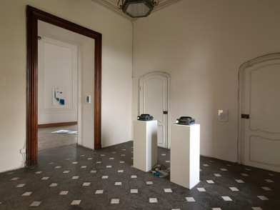 "Materia Prima - Museo d'Arte Contemporanea Castello di Rivara 2016  500 W  Two Kodak Carousel projectors on pedestals, chargers, wall Variable dimensions    Materia Prima could be seen as one of the many possible outcomes of Bepi Ghiotti's work on the neo-baroque (space of) Castle of Rivara. Only one of the possible results, reasonably, determined by having to set a time limit to his tireless research. Yet, there is a moment before, at the beginning of the artist's operation on the location, in which time has already overwhelmingly taken its share as a raw material. Bepi's trained photographer eye recognizes the majesty of time, which is manifested in the traces of life and art deposited in the Castle's ambient by the passage of time.  His work thus concentrates on an attempt to resurface the essence of this space, almost sweeping away, one after the other, all the layers of recent history.  ​  Room after room, wall after wall, Ghiotti analyzes the geometries, listening to them breathe. Like a chemist in an ancient laboratory, he captures the light coming through the windows in different hours throughout the day. The light continuously changes, as does the perception of the architectures, thus delivering an essential experience of the location, through the artist's installation. The rooms of the neo-baroque villa, similar to living organisms, bring out the primary elements of their physiology: the asynchronous pulse of the two projectors beaming pure light, installed in the entryway; along the electromagnetic vibrations captured with ancient gestures on the cyanotypes, in the partial views of faces and landscapes that can only be imagined through scratches of light, torn away from the black of darkness,  of oblivion.  ​  Through this intervention, which is almost an archaeological operation on  the location, soaked in anthropological suggestions and ancient techniques,  Bepi Ghiotti reveals the heart to the audience. The viewer is led to the ""source"" of the identity of those rooms from the Eighteen hundreds, recovered through the artist's tenacious experience inside the Caslte and that of all its physical and unworldly dwellers. Walking through those rooms, among objects revealing the essence, one has the clear feeling of being inside a fully developing process, deeply interconnected with the ponderously conquered relationship the artist has had with the Castle of Rivara, day after day, in the resounding loneliness of those huge, empty rooms."