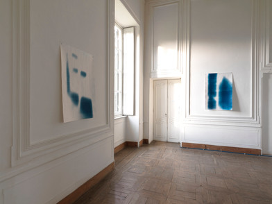 """Materia Prima - Museo d'Arte Contemporanea Castello di Rivara 2016   Cianotipi  Cyanotype on paper 122x82 cm   Materia Prima could be seen as one of the many possible outcomes of Bepi Ghiotti's work on the neo-baroque (space of) Castle of Rivara. Only one of the possible results, reasonably, determined by having to set a time limit to his tireless research. Yet, there is a moment before, at the beginning of the artist's operation on the location, in which time has already overwhelmingly taken its share as a raw material. Bepi's trained photographer eye recognizes the majesty of time, which is manifested in the traces of life and art deposited in the Castle's ambient by the passage of time.  His work thus concentrates on an attempt to resurface the essence of this space, almost sweeping away, one after the other, all the layers of recent history.    Room after room, wall after wall, Ghiotti analyzes the geometries, listening to them breathe. Like a chemist in an ancient laboratory, he captures the light coming through the windows in different hours throughout the day. The light continuously changes, as does the perception of the architectures, thus delivering an essential experience of the location, through the artist's installation. The rooms of the neo-baroque villa, similar to living organisms, bring out the primary elements of their physiology: the asynchronous pulse of the two projectors beaming pure light, installed in the entryway; along the electromagnetic vibrations captured with ancient gestures on the cyanotypes, in the partial views of faces and landscapes that can only be imagined through scratches of light, torn away from the black of darkness,  of oblivion.    Through this intervention, which is almost an archaeological operation on  the location, soaked in anthropological suggestions and ancient techniques,  Bepi Ghiotti reveals the heart to the audience. The viewer is led to the """"source"""" of the identity of those rooms from the Eighteen hundreds, reco"""